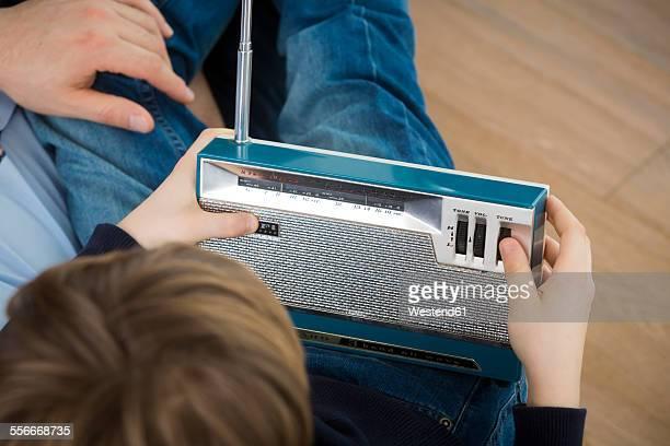 father and son listening to an old radio - radiogerät stock-fotos und bilder
