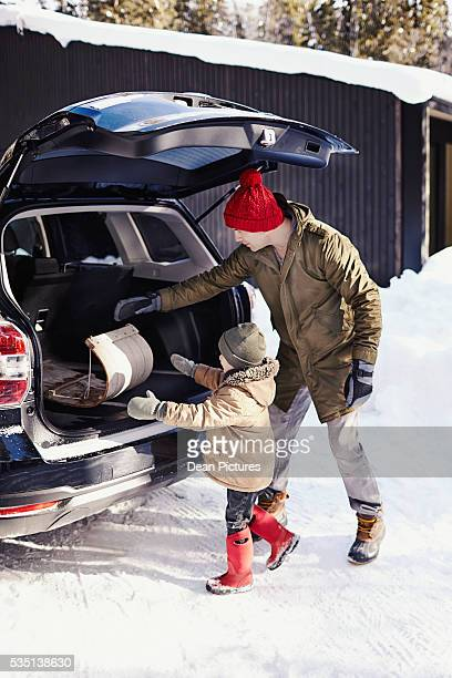Father (30-34) and son (4-5) load the car