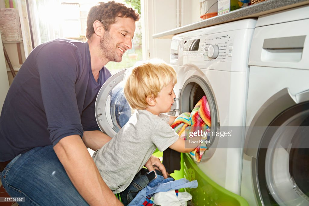 Father and son loading washing machine : Stock-Foto