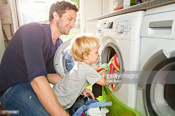 father and son loading washing machine - waschen stock-fotos und bilder