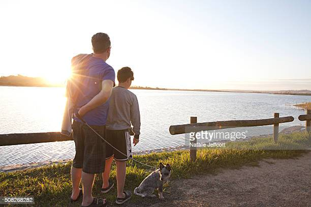 A Father and son look across water at sunset