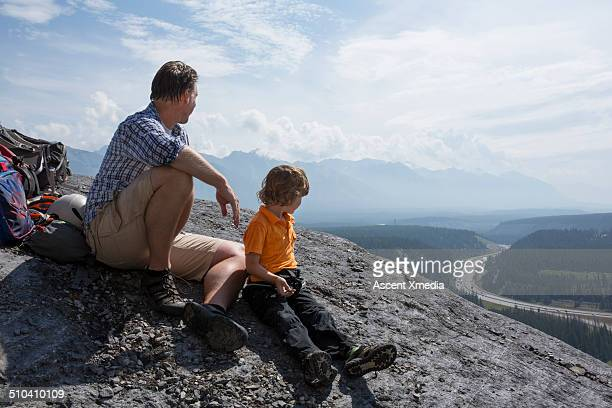 Father and son look off from top of mountain hike