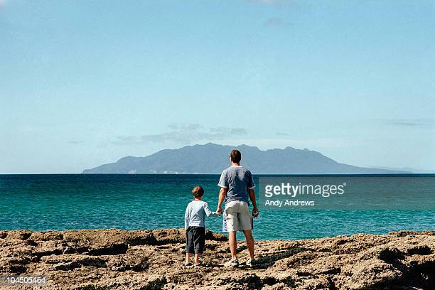 Father and son look out to sea