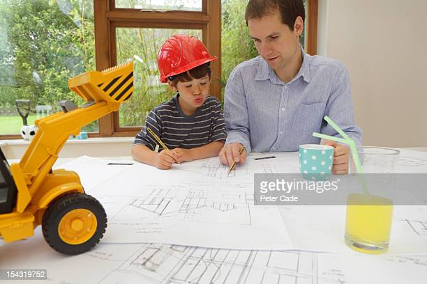 Father and son looking at architect plan for house