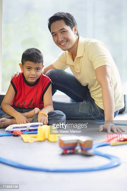 Father and son looking at camera, toy train set on floor in front of them