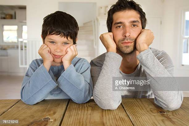 Father and son looking at camera, with hands on cheeks