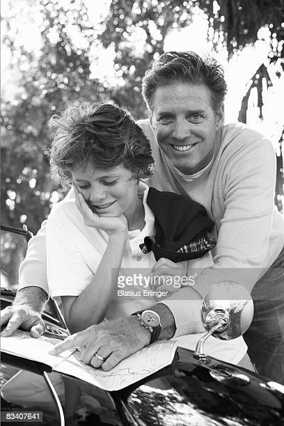 father and son looking at map - blasius erlinger stock pictures, royalty-free photos & images