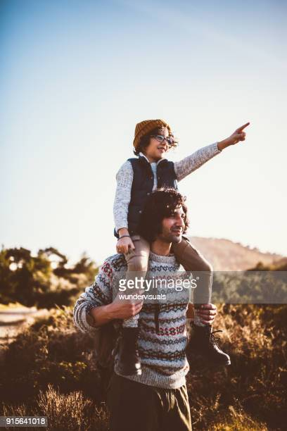 Father and son looking at mountain view on hiking trip