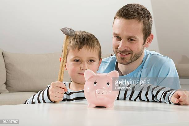 Father and son (4-5) looking at piggybank, boy holding hammer