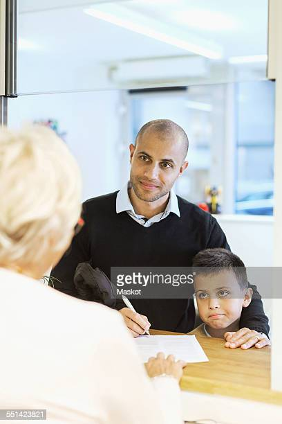 Father and son looking at receptionist while filling forms in orthopedic clinic