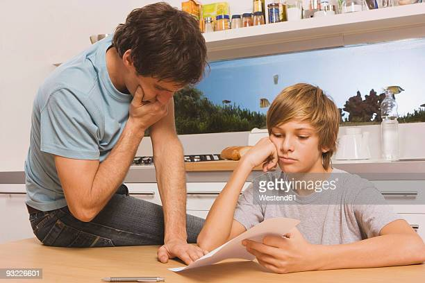 Father and son (13-14) looking at report card, hands to chin