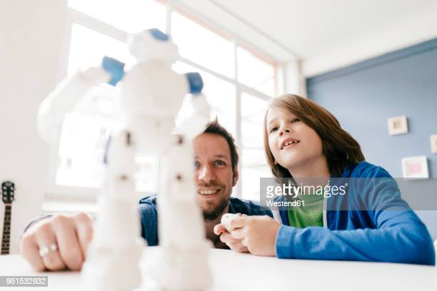 Father and son looking at robot on table at home