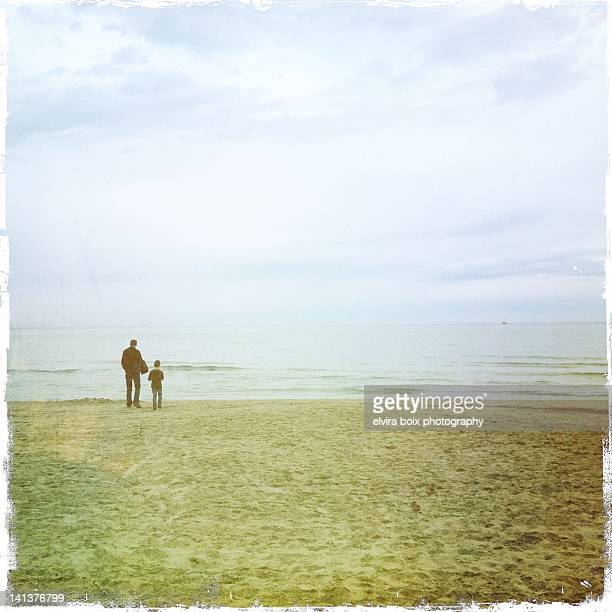 father and son looking at sea - mid distance stock pictures, royalty-free photos & images