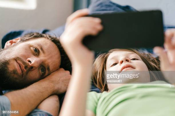 father and son looking at smartphone together at home - stream stock pictures, royalty-free photos & images