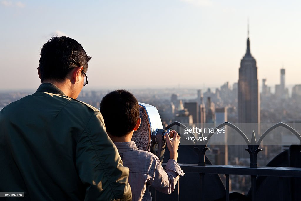 CONTENT] Father and son looking at the Empire State Building from the Top of The Rock. Manhattan, New-York City