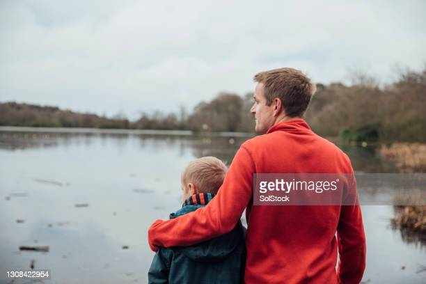 father and son looking at the view - genderblend stock pictures, royalty-free photos & images