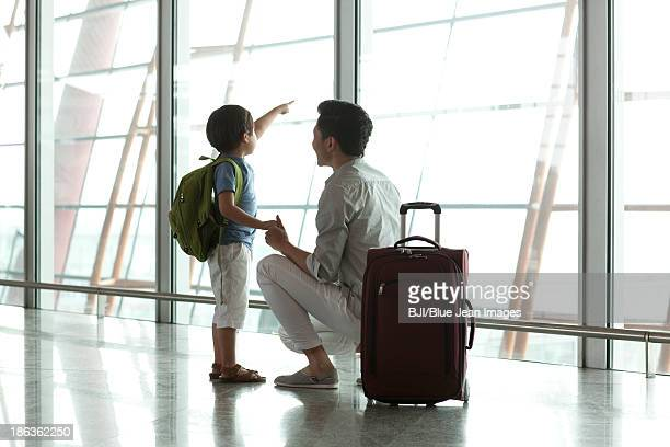 Father and son looking at view at the airport