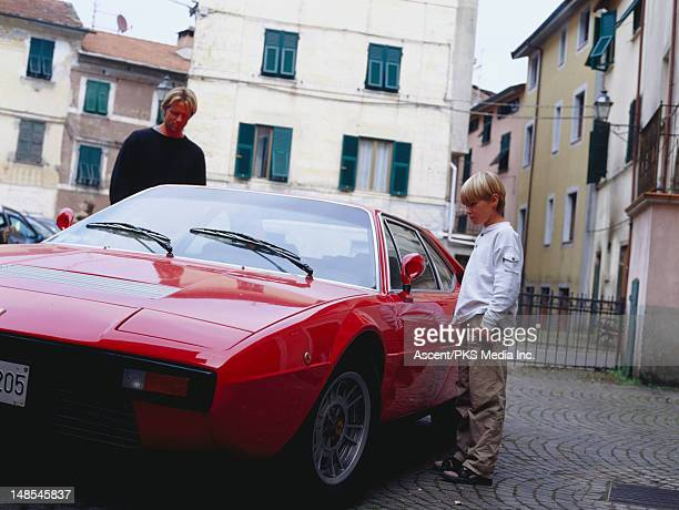 father and son looking at vintage ferrari. - ferrari stock pictures, royalty-free photos & images
