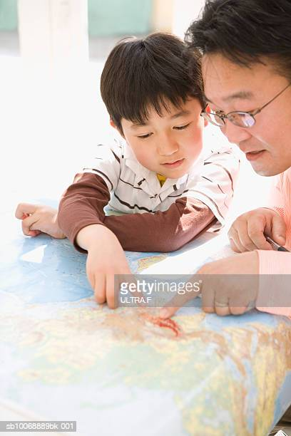 Father and son (8-9) looking at world map