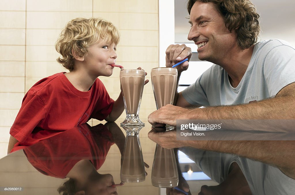 Father and Son Looking Face to Face Drinking a Chocolate Milkshake : Stock Photo