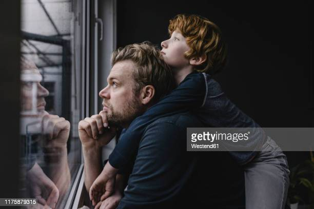 father and son looking out of window on rainy day - simple living stock pictures, royalty-free photos & images