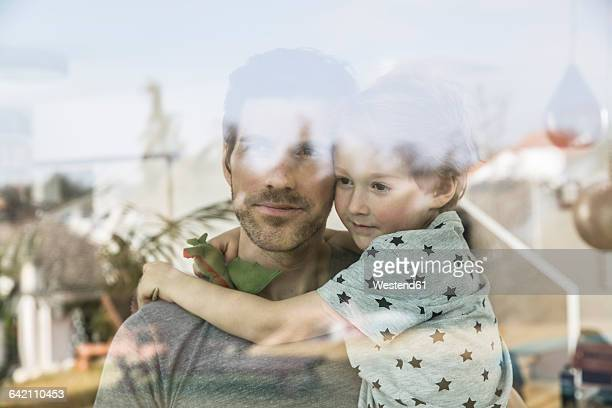 Father and son looking out of window