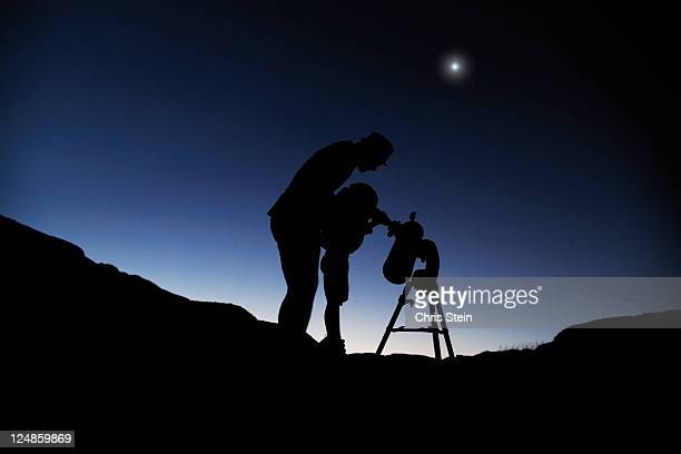 Father and son looking through a telescope
