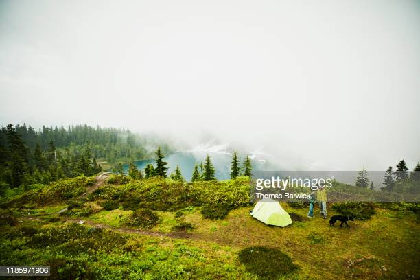 Father and son looking up at mountains while standing beside tent during backpacking trip