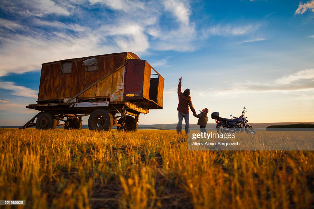 Father and son looking up from autumn field at sunset, Sarsy Village, Sverdlovsk Oblast, Russia : Stock Photo