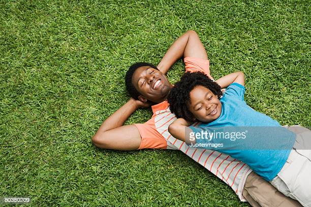 Father and son lying down on grass