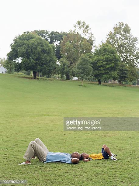 father and son (5-7) lying on grass in park, side view - piedmont park atlanta georgia stock pictures, royalty-free photos & images