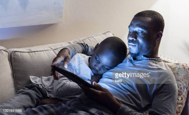 father and son lying on sofa using digital tablet - homemaker stock pictures, royalty-free photos & images