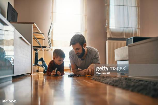 father and son lying together on the floor playing with toy cars - toy car stock pictures, royalty-free photos & images