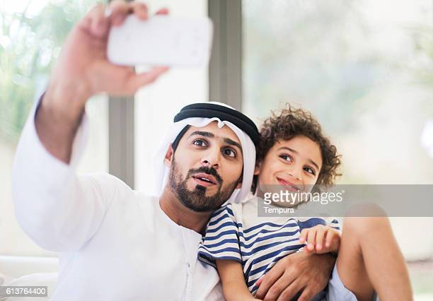 Father and son making a selfie with a smartphone.