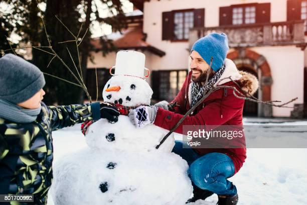 père et fils, faire un bonhomme de neige - bonhomme de neige photos et images de collection
