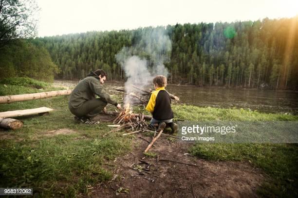father and son making campfire on field by river - freizeitaktivität im freien stock-fotos und bilder