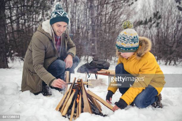 Father and son making campfire on the snow