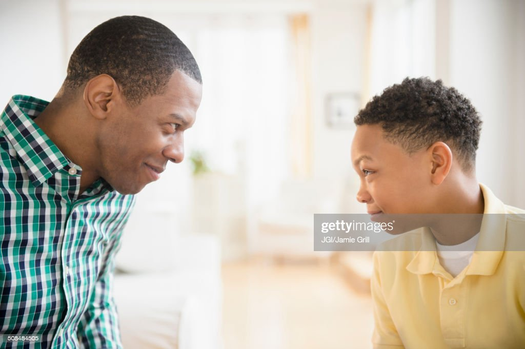 Father and son making faces at each other : Stock Photo