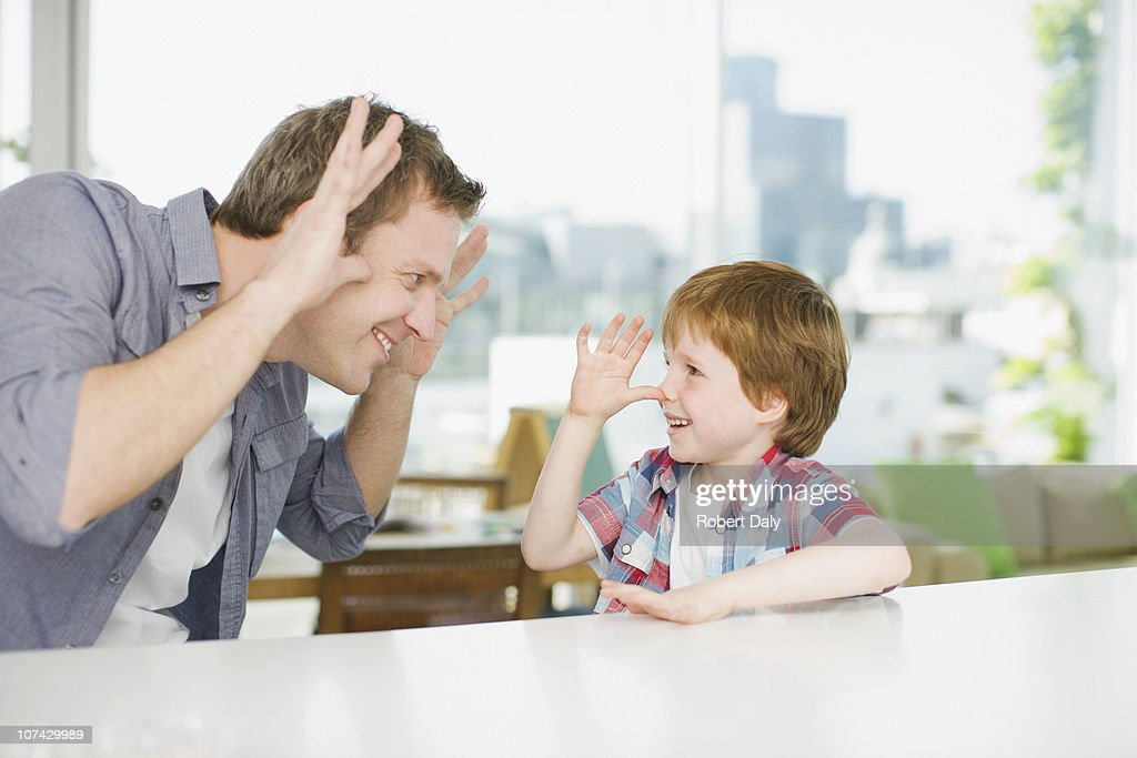Father and son making faces at one another : Stock Photo