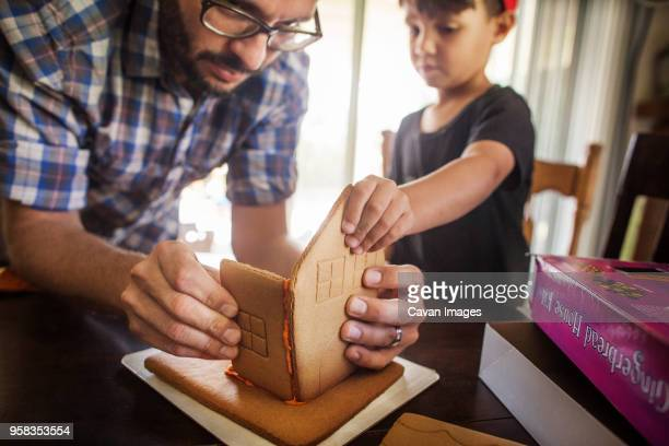 father and son making gingerbread house at home - concentration stock pictures, royalty-free photos & images