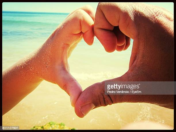 Father and son making heart shape of hands at beach