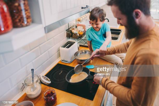 father and son making pancakes at home - pancakes stock pictures, royalty-free photos & images