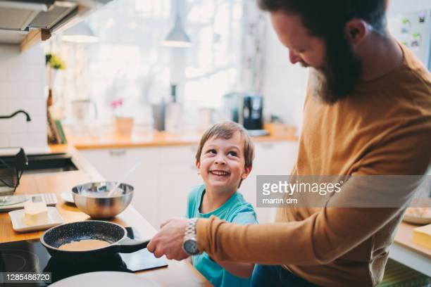 father and son making pancakes - pancakes stock pictures, royalty-free photos & images