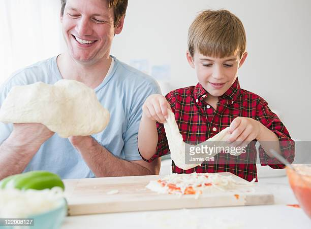 Father and son making pizza together