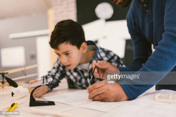 Father and son making toy plane