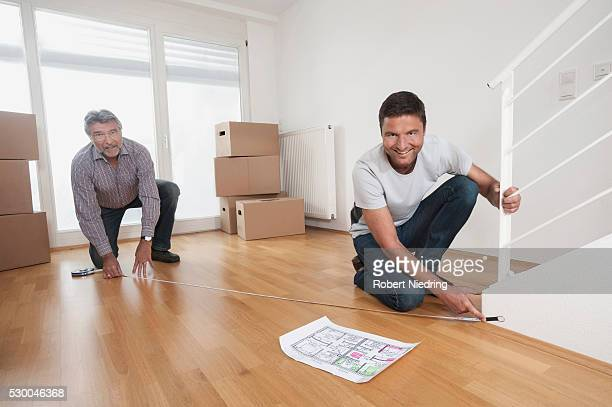 Father and son measuring wooden floor in new home, Bavaria, Germany