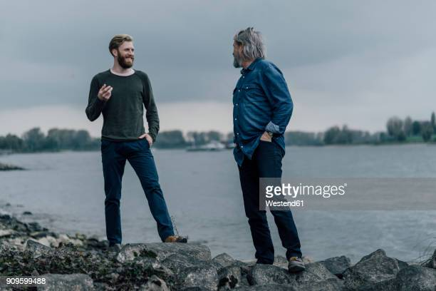 father and son meeting at rhine river in autmn, talking together - seulement des hommes photos et images de collection