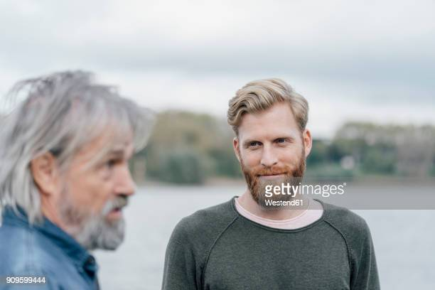 father and son meeting outdoors, portrait - respekt stock-fotos und bilder