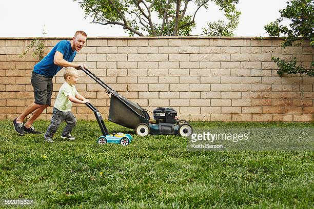 father and son mowing lawn in backyard - imitation stock pictures, royalty-free photos & images