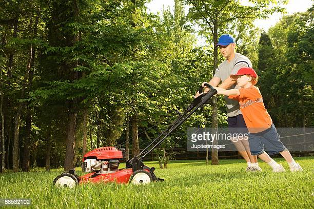 Father and son mowing lawn
